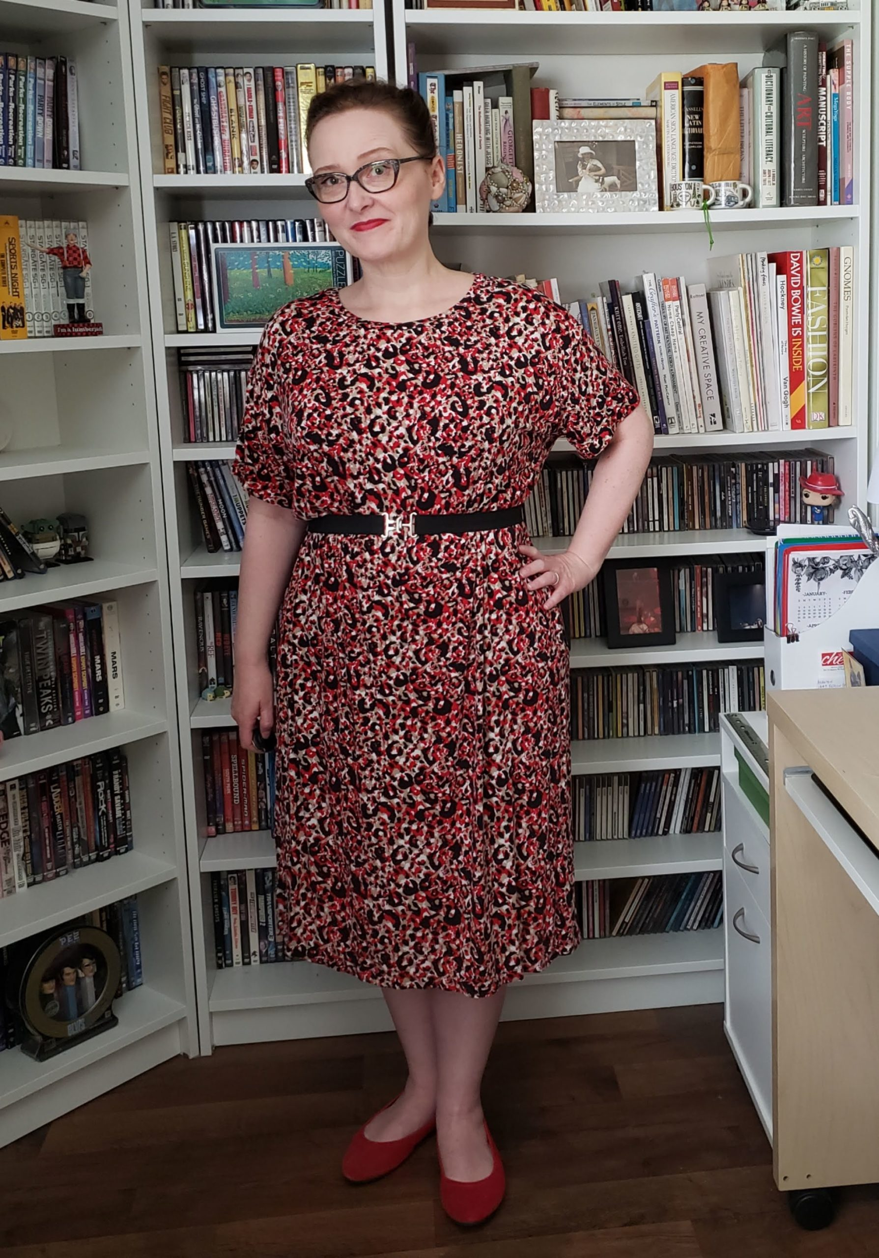 Sarah, a short, average-sized person, wears a black and red print 80s style t-shirt dress.